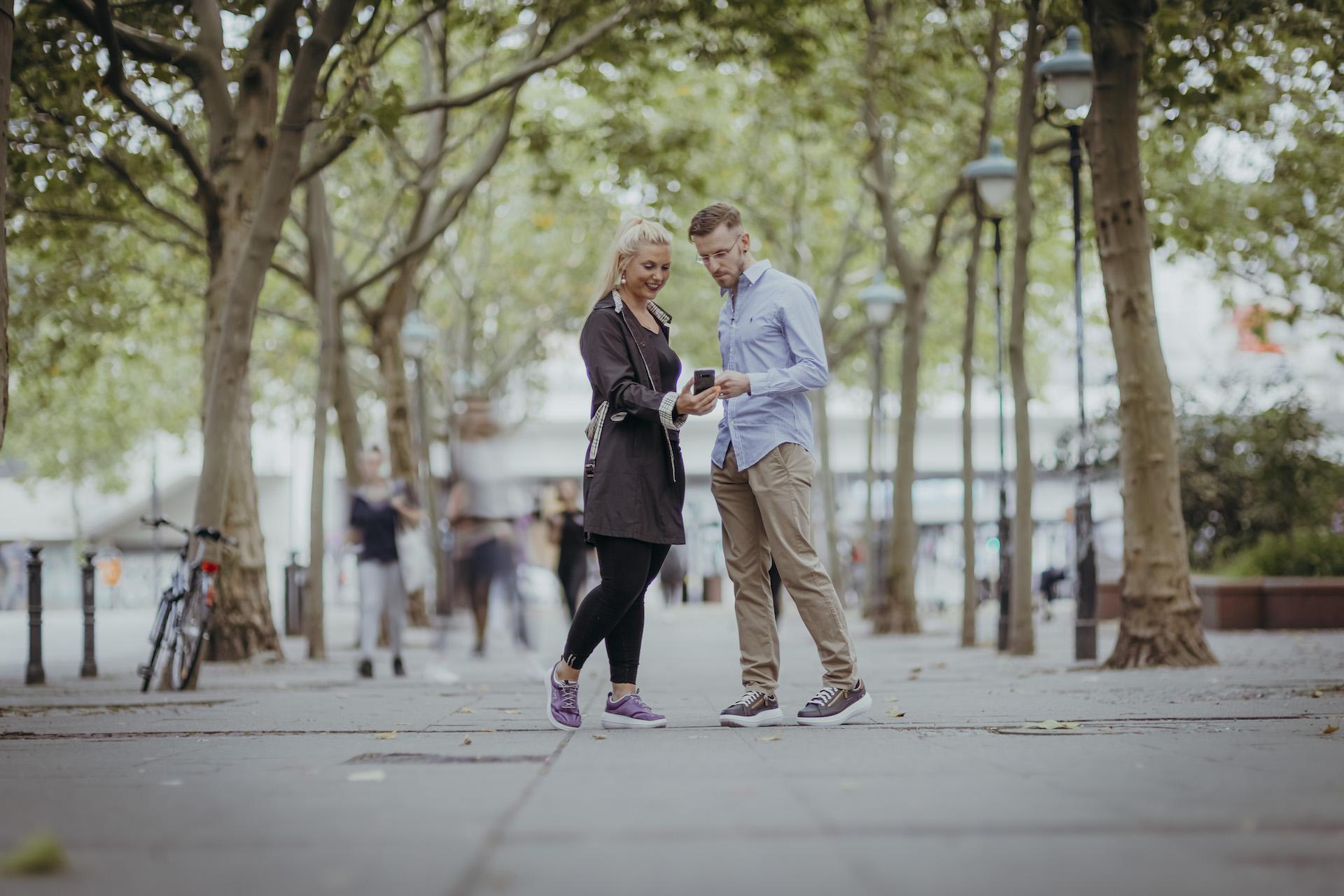 Zwei Menschen mit kybun-Schuhe in der Stadt unter Platanen